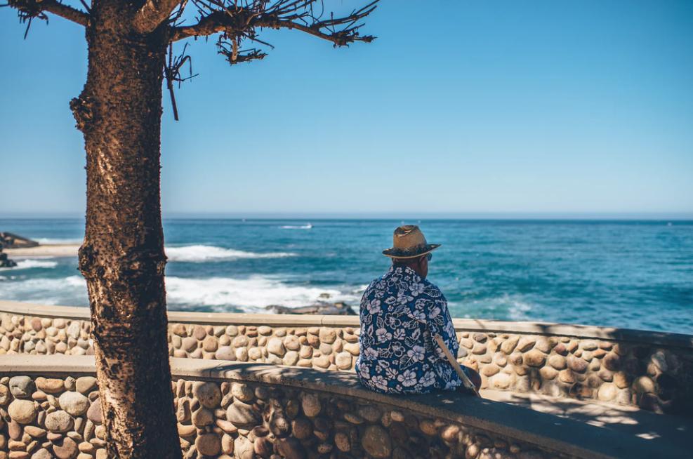 Hombre mayor viendo el mar en verano.